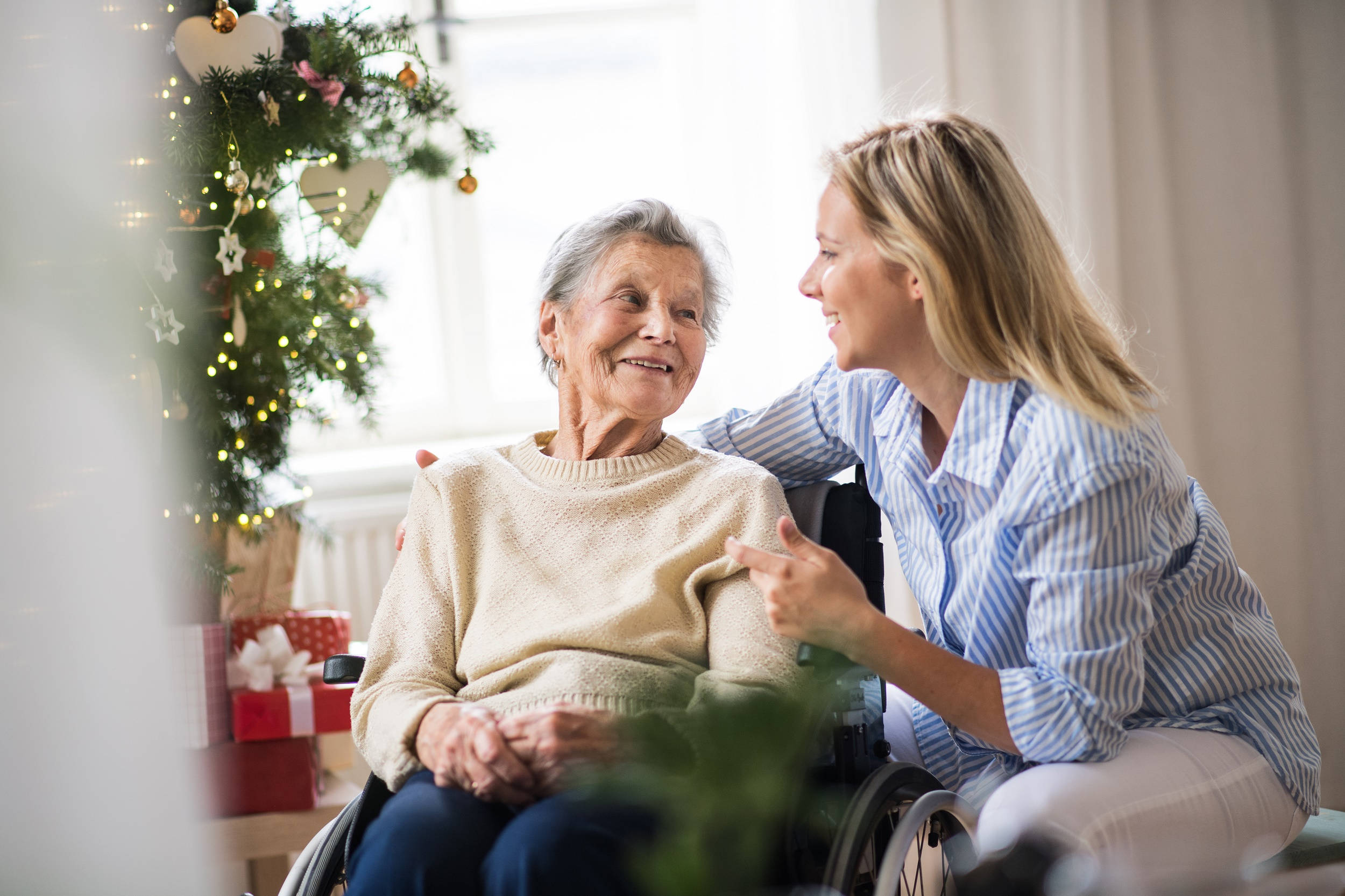 Care assistant comforts older person in wheelchair next to Christmas tree