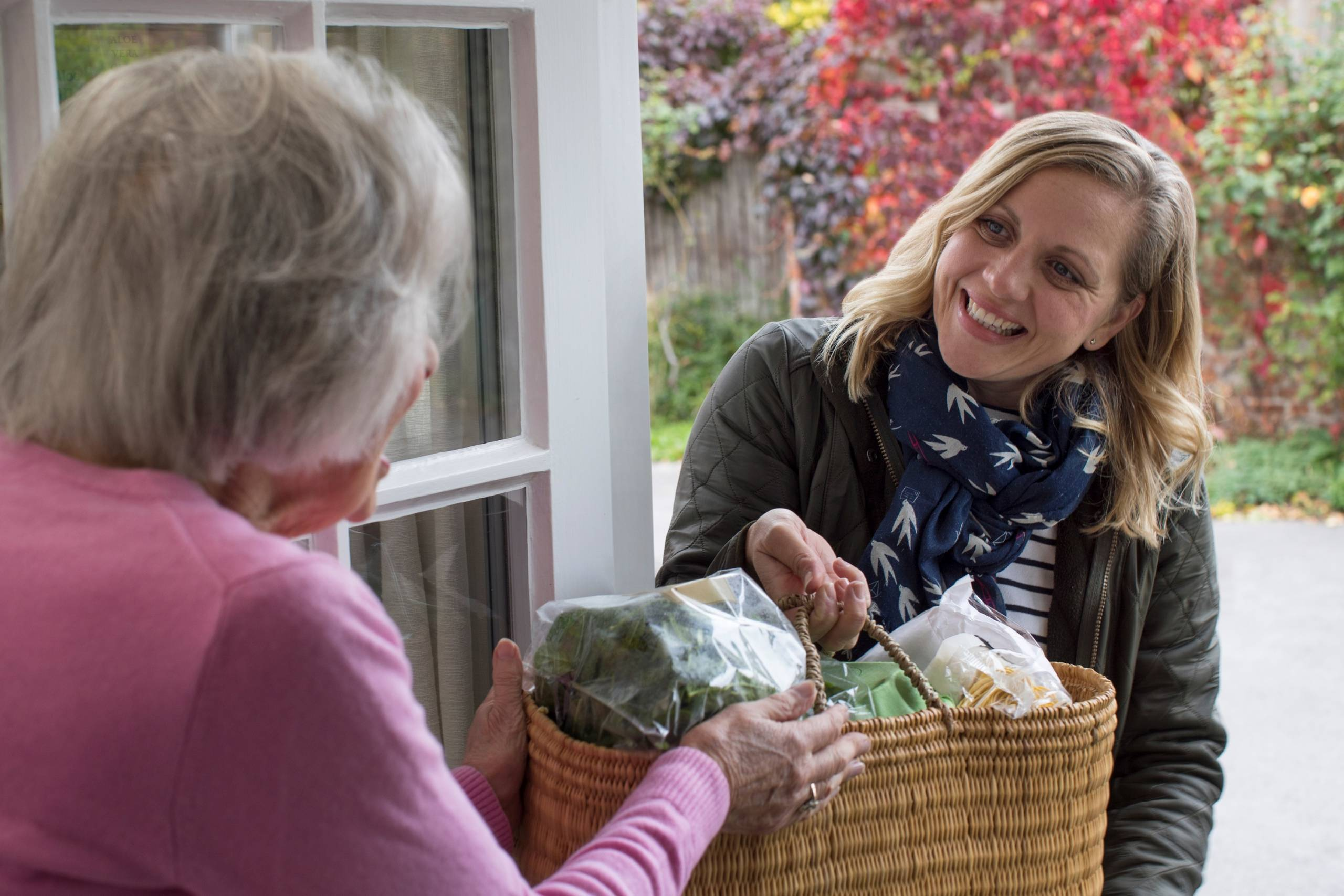 volunteer helping elderly neighbour with food shopping