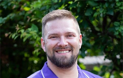 male carer wearing purple uniform