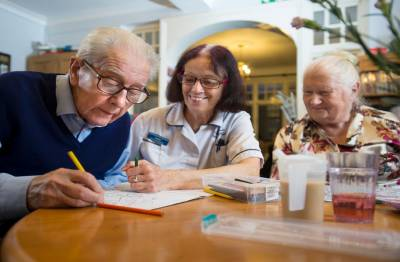 Female carer sat at table with residents playing a game